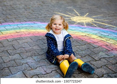 Happy little toddler girl in rubber boots with rainbow sun and clouds with rain painted with colorful chalks on ground or asphalt in summer. Cute child having fun. creative leisure