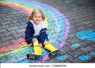 Happy little toddler girl in rubber boots with rainbow painted with colorful chalks on ground during pandemic coronavirus quarantine. Children painting rainbows along with the words Let's all be well