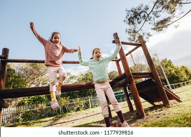 Happy little twin sisters jumping off a wooden log at the park  Little girls having fun on outdoor playground.