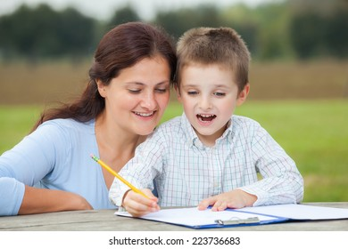 Happy little young boy in white shirt and his smiling mother write or draw with a pencil on a sheet of paper on wood table in the park