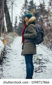 Happy lonely attractive young girl in warm clothing with backpack standing in forest or park and looking back. Single woman loves to walk alone on snow covered road. Hiking, enjoying fresh air