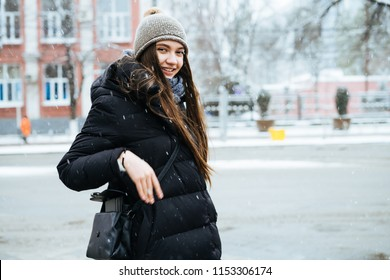 happy long-haired girl in a warm black jacket and hat walks through the winter city, it's cold
