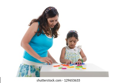 happy looking indian mother and daughter learning with educational toy