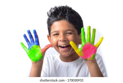 Happy looking kid playing with paints in his fingers.