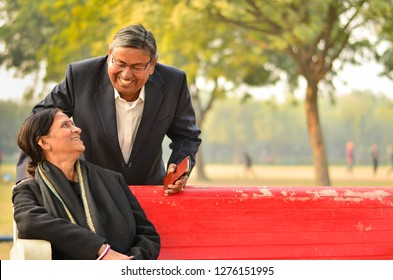 Happy looking retired senior Indian man and woman couple smiling and looking at each other sitting on a park bench
