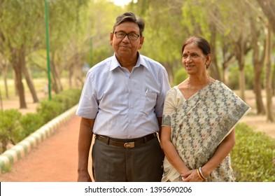 Happy looking retired senior Indian man and woman couple smiling and posing in a park outdoor setting in Delhi, India. Concept love