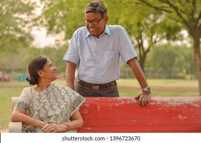 Happy looking retired senior Indian man and woman couple, sitting on a red bench, smiling and looking at each other in a park outdoor