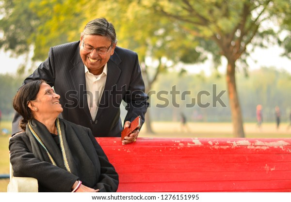 Happy looking retired senior Indian man and woman couple smiling and looking at each other sitting on a park bench in New Delhi, India