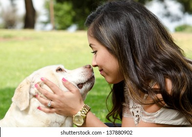 a happy looking woman nose to nose with her pet dog.