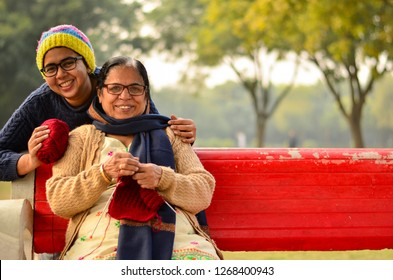 Happy looking young Indian woman with her mother knitting sweater who is sitting on a red bench in a park in New Delhi, India. Concept Mother's day
