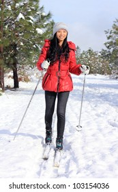 A happy looking young woman cross country skiing through fresh snow