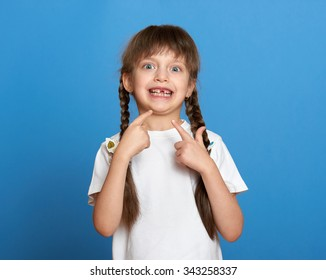 happy lost tooth girl portrait, studio shoot on blue background