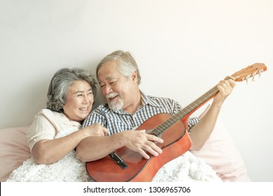 Happy love Elderly couple smile face, Senior couple old man and senior woman relax playing acoustic guitar in bed room - lifestyle senior concept