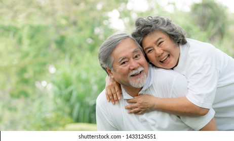 Happy love Elderly couple smile face , Senior couple old man and senior woman relaxing hug in a forest