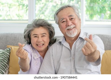 Happy love Elderly couple smile face , Senior couple old man and senior woman relaxing show heart sign in Their home