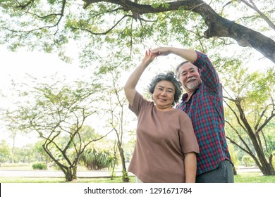 Happy love Elderly couple smiley face , Senior couple old man and senior woman relax dancing a forest - lifestyle senior concept