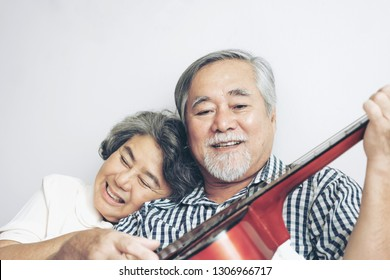Happy love Elderly couple smiling , Senior couple old man and senior woman relax playing acoustic guitar in bed room - lifestyle senior concept