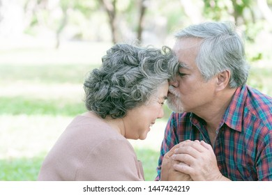 Happy love Elderly man kissing on forehead of his couple with sweet romantic, his wife has smile face with happy, Senior Asian couple hands in hands at park