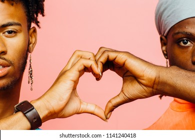 Happy love/ Two men making a heart shape with their hands, isolated on pink studio background
