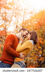 Happy and in love. Young cute couple in love staying and kissing on the autumn park on sunset