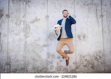 Happy and in love. Happy young man in smart jacket holding bouquet of flowers and jumping in front of the concrete wall