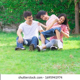 Happy lovely beautiful Asian family father, mother and son playing together at home garden. Smiling parent and cheerful kid relax and enjoy activity or leisure on summer holiday together.