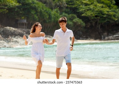 happy lovely caucasian couple running on tropical beach