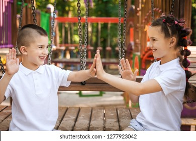 happy lovely children sitting and clapping hands at the playground. concept of summer, childhood and leisure.
