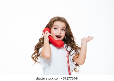 Happy lovely little girl talking on telephone and holding copyspace on palm over white background