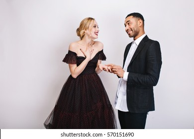 Happy lovely moments of cute couple of handsome guy making proposal of marriage to beautiful blonde young woman in luxury dress on white background. Expressing happiness, in love, Valentine`s day