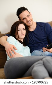 happy and lovely  young couple at home in sofa watching tv together