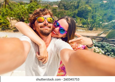 Happy lovers,  attractive woman and man traveling  in tropical island enjoying romance.  Attractive couple  making selfie, smiling and have fun together.