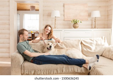 Happy lovers newlyweds enjoying a weekend in the room of their cozy country house sitting on the sofa with their beloved dog