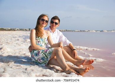 Happy lovers on beach of pink lake. Smiling young woman and man in nature.
