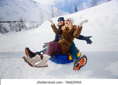 Happy lovers people on sled outdoors in mountains in winter snow. Concept of Christmas holidays