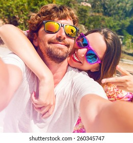 Happy lovers, woman and man traveling on vacation travel in tropical island enjoying romance.  Attractive couple  making selfie, smiling and have fun together. Instagram filter.