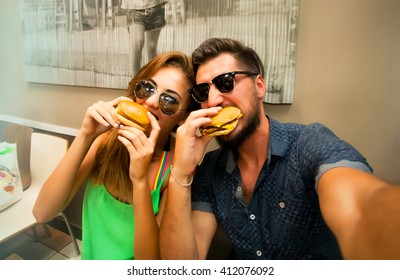Happy lovers,attractive woman and man traveling in tropical island enjoying romance. Attractive couple making selfie,smiling and have fun together.Couple Eating big burgers,cheeseburger and coke.fun