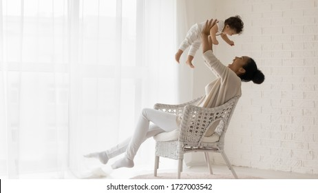 Happy loving african American young mother sit in chair at home relax play with funny little newborn baby girl, smiling biracial mom have fun lift in air enjoy family weekend with cute infant child