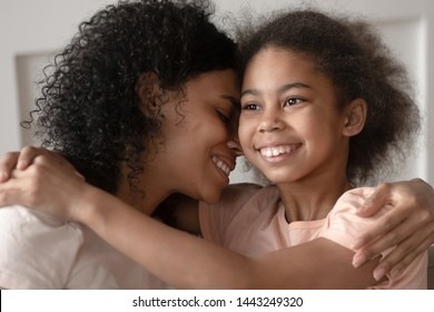 Happy loving biracial mother and small daughter hug cuddle on couch having tender moment together, smiling african American mom and girl child embrace caress reunited or reconciled after parting