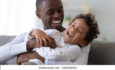 Happy loving black father embracing tickling cute african kid laughing cuddling small son sit on sofa, cheerful little child boy having fun playing with happy daddy bonding enjoy fathers day together