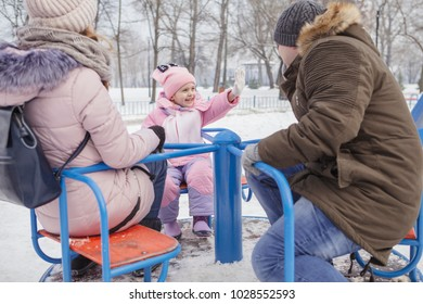 Happy loving caucasian family of mother father and daughter play, having fun in winter snowy park. Cute little girl playing
