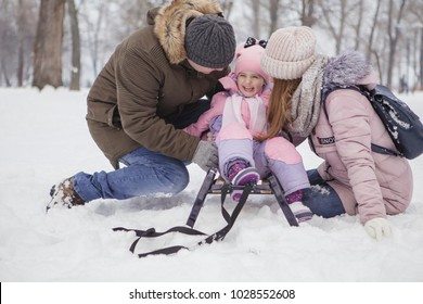 Happy loving caucasian family of mother father and daughter play, having fun in winter snowy park