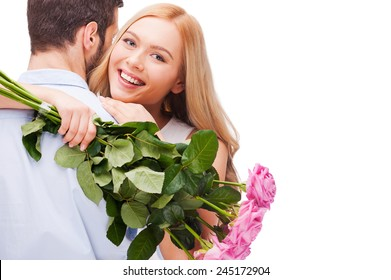 Happy loving couple. Beautiful young loving couple hugging while woman holding bouquet of pink roses and smiling and both standing isolated on white background