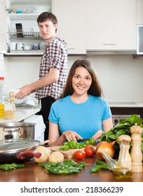 Happy loving couple cooking at table in domestic kitchen