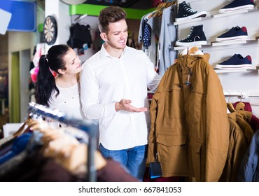happy loving couple deciding on warm suit in sports store
