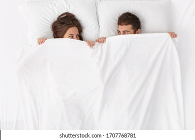 Happy loving couple have fun in bed, look from under blanket, enjoy romantic moment at home, have good relationships, spend leisure time weekend together, wake up after passionate night or sex
