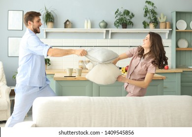 Happy loving couple having fun while having a pillow fight in the living room.