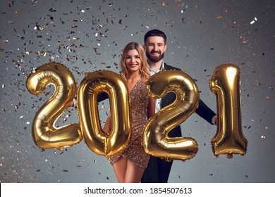 Happy loving couple holds gold 2021 balloons on grey background. New Year celebration. Holidays, festive and party concept.