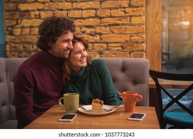 Happy loving couple hugging and laughing. They are sitting in cozy restaurant with relaxation