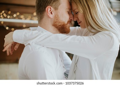Happy and loving couple kissing in the room
